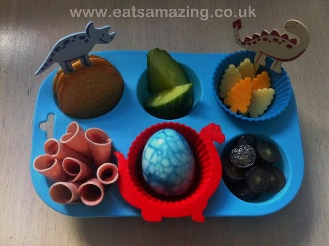 Dinosaur lunch made with dinosaur teeth, dinosaur egg, dinosaur sandwich, meat, and grapes.