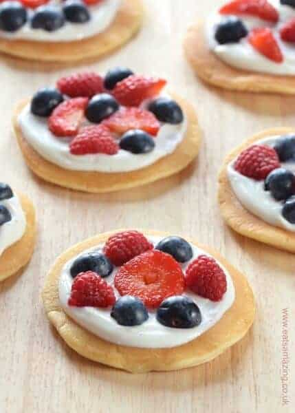 Mini fruit pizzas topped with yogurt and berries - a great easy recipe to cook with kids this summer - fun food for kids from Eats Amazing UK