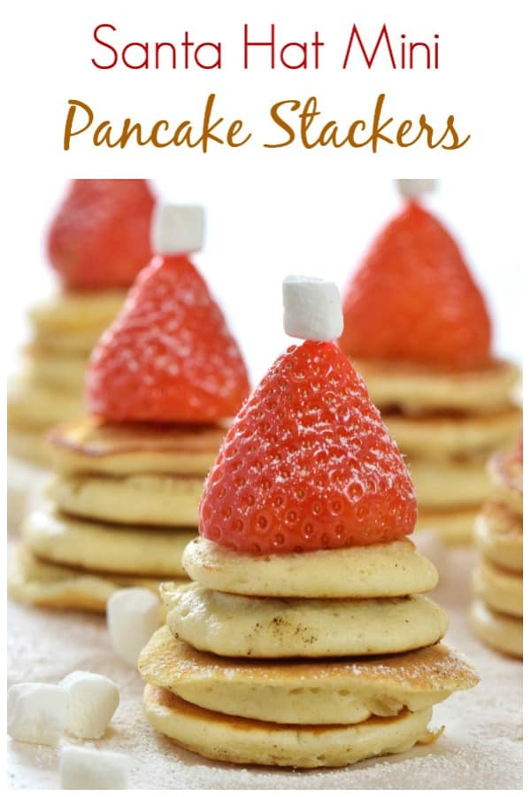 These mini pancake stackers topped with strawberry Santa hats make a really fun Christmas breakfast for kids. Perfect for a North Pole breakfast too! #EatsAmazing #Christmas #christmasfood #breakfast #pancakes #Santa #funfood #kidsfood #foodart #festive #festivefood #fatherchristmas #easyrecipe #healthykids
