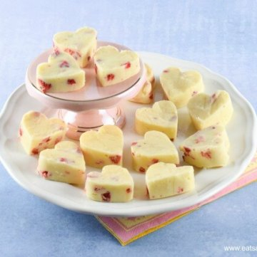 Strawberries and Cream White Chocolate Fudge Hearts on a white plate and pink mini cake stand with a pale blue background