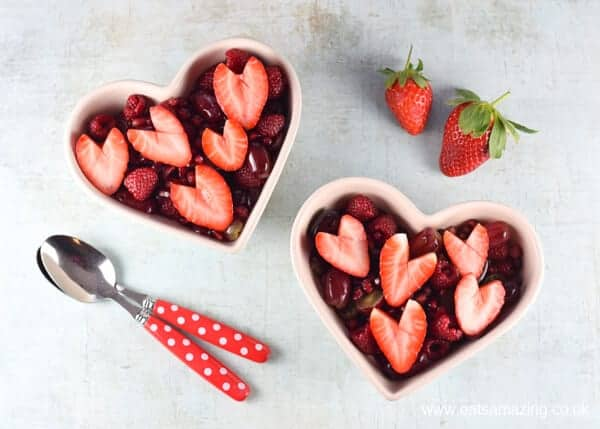 Easy fruit salad with strawberry hearts for Valentines day - in white heart shaped bowls with spoons and strawberries