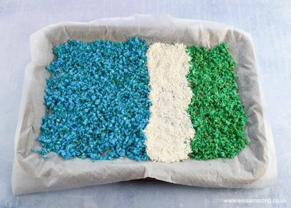 Blue white and green ocean coloured homemade coconut sprinkles drying out in a lined baking tray