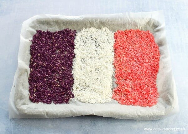 purple white and pink coloured homemade princess coconut sprinkles drying out in a lined baking tray
