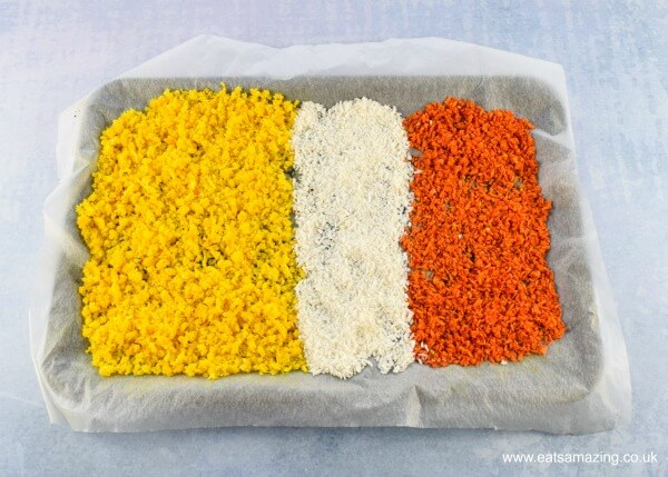 Yellow white and orange sandy beach coloured homemade coconut sprinkles drying out in a lined baking tray