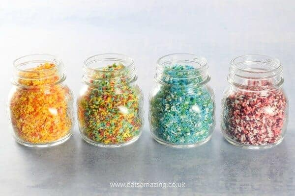 Homemade coconut sprinkle mixes in 4 glass jars in a row - ocean blue, princess pink and purple, yellow sandy beach and rainbow mixes