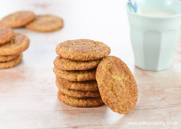 Stack of homemade snickerdoodle cookies on a wood background with a pale blue cup of milk