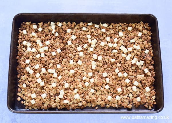 Easy strawberries and cream granola recipe - step 3 add white chocolate chunks to the cooked granola