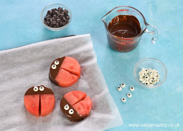 How to make watermelon ladybirds - step 3 dip the tops in melted dark chocolate to make the heads