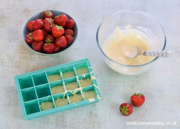 How to make white chocolate covered strawberry cubes - step 1 melt the chocolate and spoon into the ice cube tray