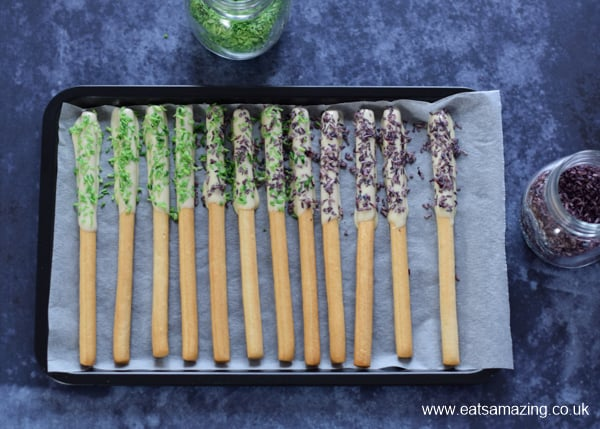 Edible Monster Breadstick Wands recipe - step 2 sprinkle with homemade Halloween coconut sprinkles