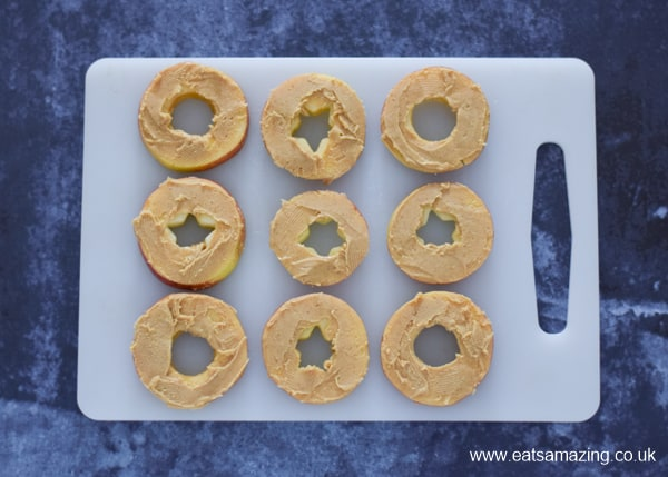 Fun and healthy Halloween food for kids - monster apple donuts recipe - step 3 spread apple slices with peanut butter