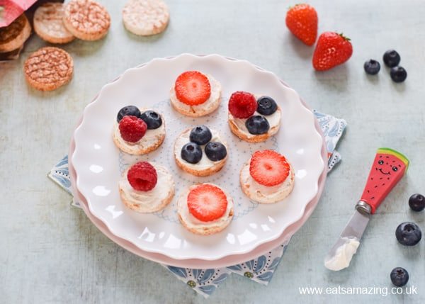 Top mini rice cakes with cream cheese and berries for a delicious healthy snack kids will love