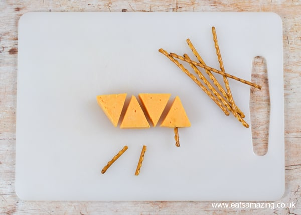 How to make a simple cheese Christmas trees snack - step 2 add pretzel stick trunks