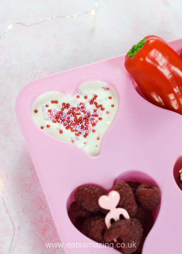 Cute heart themed muffin tin meal for kids - fun Valentines food idea - yogurt with pink and red sprinkles