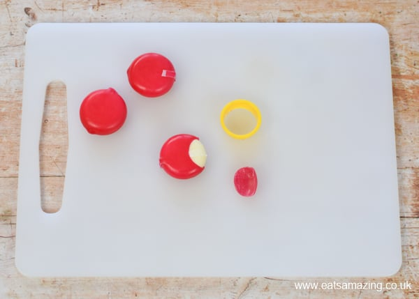 How to make a Babybel cheese ladybug - step 1 use a mini circle cutter to remove a semi-circle from the wax for the head