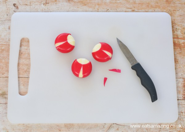How to make a Babybel cheese ladybug - step 2 cut triangle slithers from the wax to form the bug wings