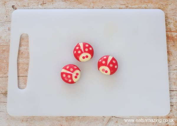 How to make a Babybel cheese ladybug - step 4 add eyes with some of the wax circles you removed to make spots