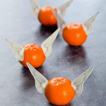 Easy and healthy Harry Potter themed party food idea - orange edible snitches with free wings printable