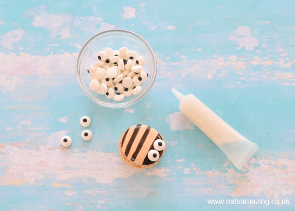 How to make cute bee macarons - step 2 glue on candy eyeballs with icing