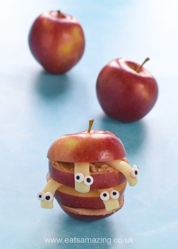 Fun kids snack of sliced apple with peanut butter and cheese worms sticking out