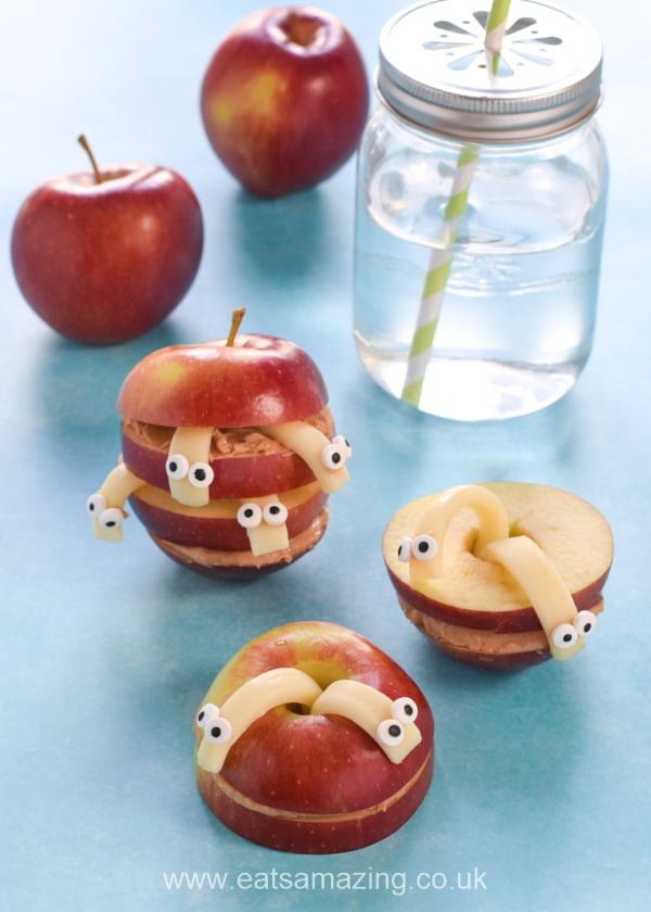 Stacked apple and peanut butter slices with cheese worms and a glass of water
