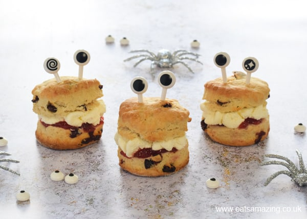 Monster scones with jam and whipped cream with silver spiders in the background