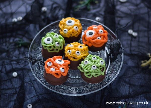 Halloween dessert idea - monster tea cakes on a glass cake stand with dark background