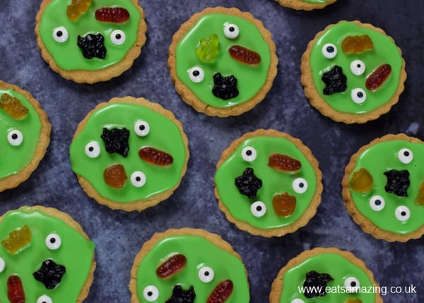 Lots of green swamp monster themed Halloween cookies from above on a dark backdrop