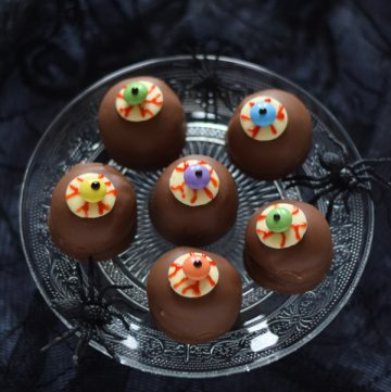 6 eyeball teacakes on a glass cake stand with dark background