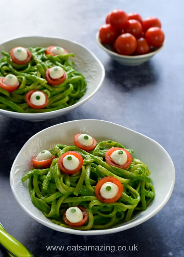 2 bowls of green monster spinach pesto pasta with cheese and tomato eyeballs