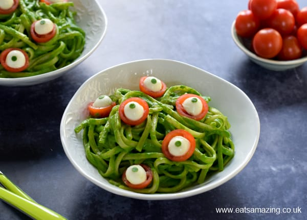 Bowl of green monster spinach pesto pasta with cheese and tomato eyeballs