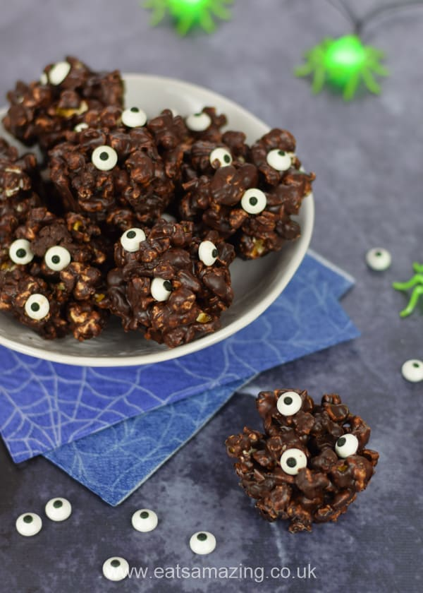 Bowl of monster chocolate popcorn balls with scattered candy eyeballs and spider fairy lights in the background