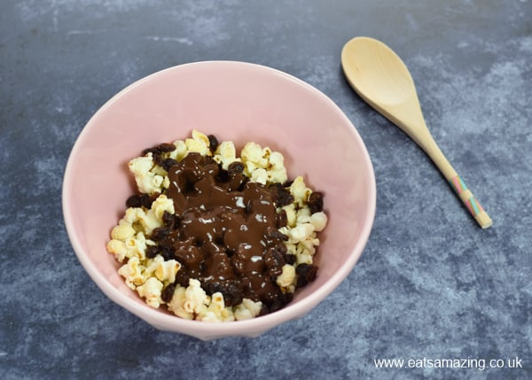 Bowl with popcorn and melted chocolate in with wooden spoon on the side