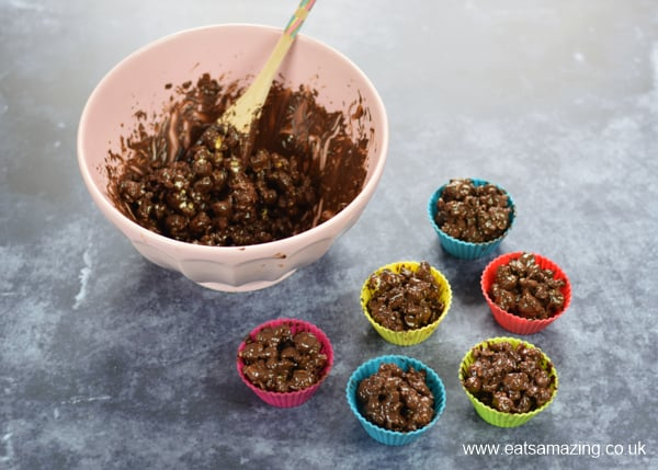 Bowl of chocolate covered popcorn with silicone muffin cups on the side filled with the popcorn ball mixture