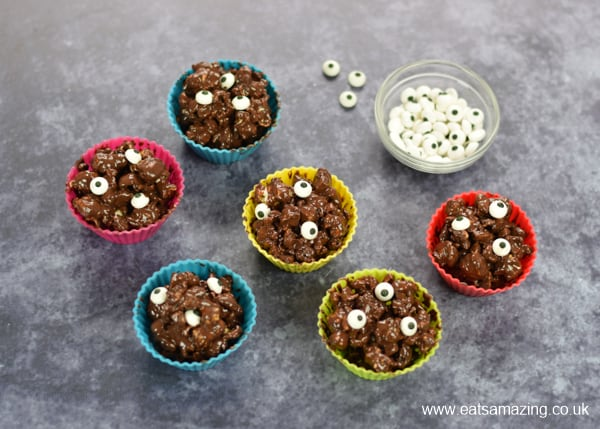 chocolate covered popcorn balls in silicone muffin cups with candy eyeballs to turn them into Monsters for Halloween