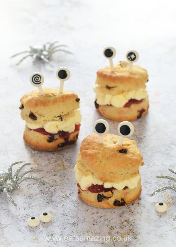 3 jam and cream scones with monster googly eyes and decorative spiders in the background