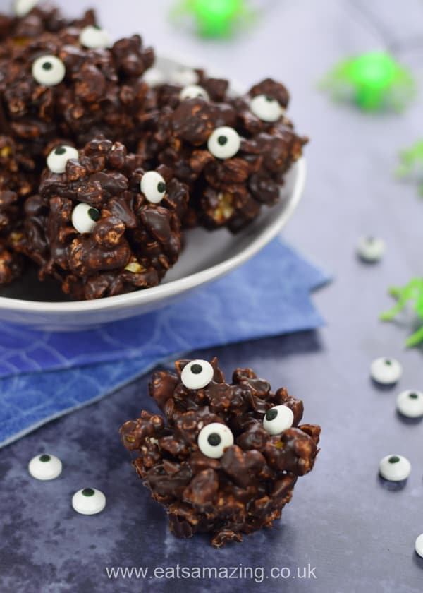 Single monster popcorn ball with a bowl of popcorn balls behind and scattered candy eyeballs