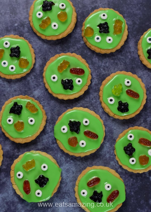 Swamp monster cookies topped with green icing and halloween sweets on a dark backgrond
