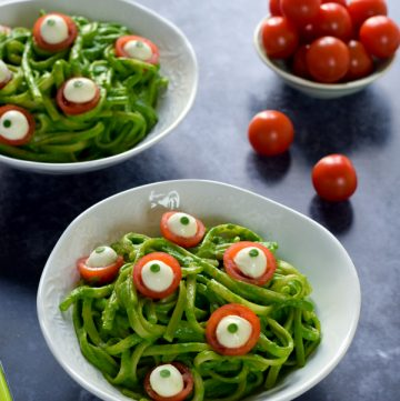 2 bowls of green monster spaghetti topped with cheese and tomato eyeballs with a bowl of cherry tomatoes