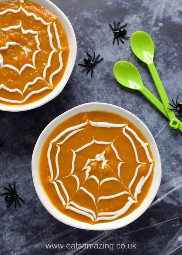 Halloween pumpkin soup with yogurt spider webs in white bowls with toy spiders