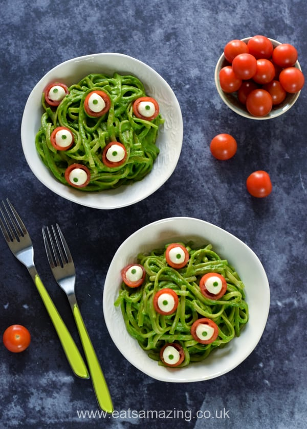 Two bowls of green monster spaghetti with edible eyeballs, cherry tomatoes and forks