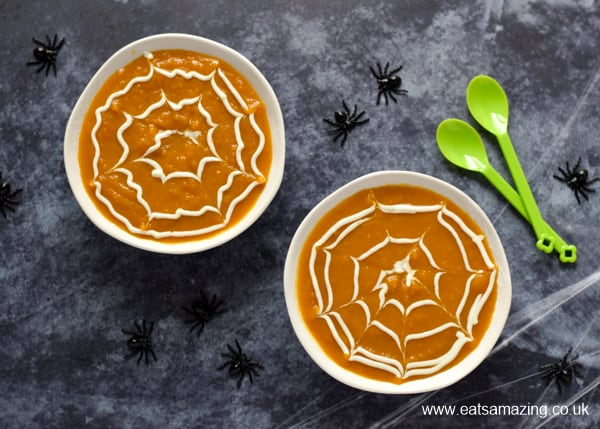 Halloween pumpkin spider web soup in white bowls with green spoons on a grey back ground