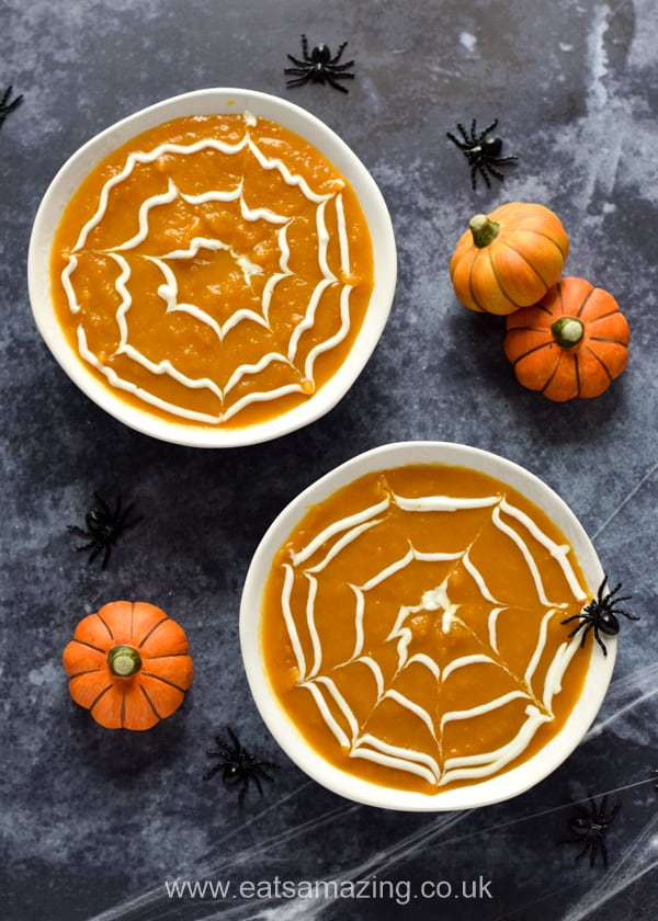 spider web pumpkin soup in white bowls with mini pumpkin decorations