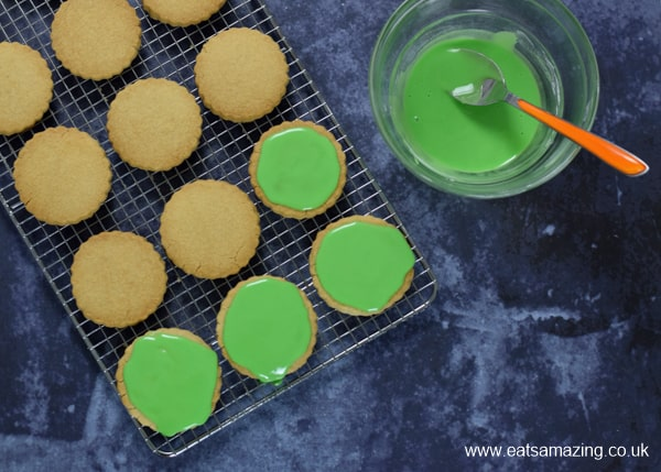 Topping shortbread cookies with green icing on a cooling rack