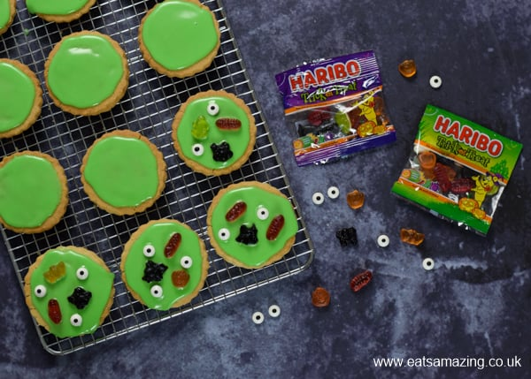 Topping our swamp monster Halloween cookies with haribo trick or treat sweets and candy eyeballs