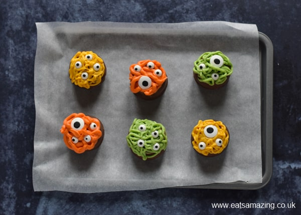 6 Halloween monster tea cakes on a lined baking tray ready for chilling