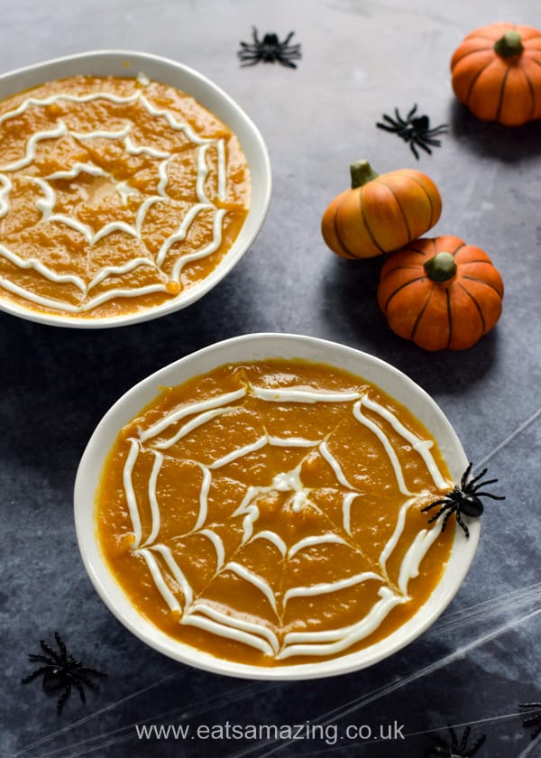 Easy pumpkin soup with yogurt spider webs, toy spiders and mini pumpkin decorations on a dark background