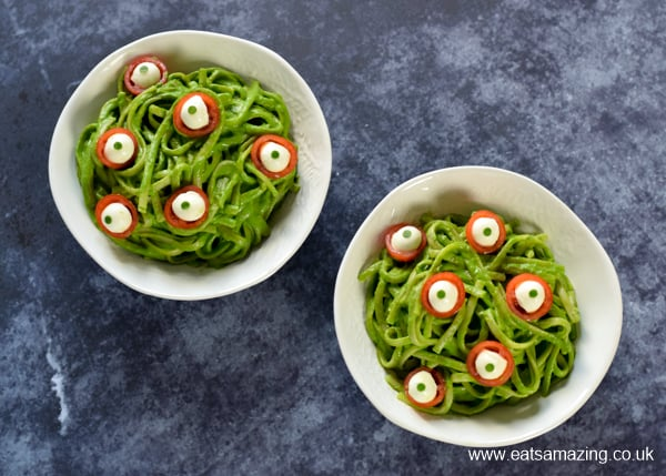 2 bowls of green monster spaghetti topped with cheese and tomato eyeballs