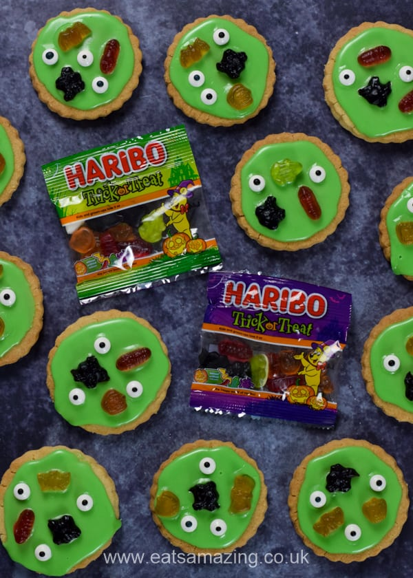 Haribo trick or treat sweet packets with swamp monster themed cookies on a dark background