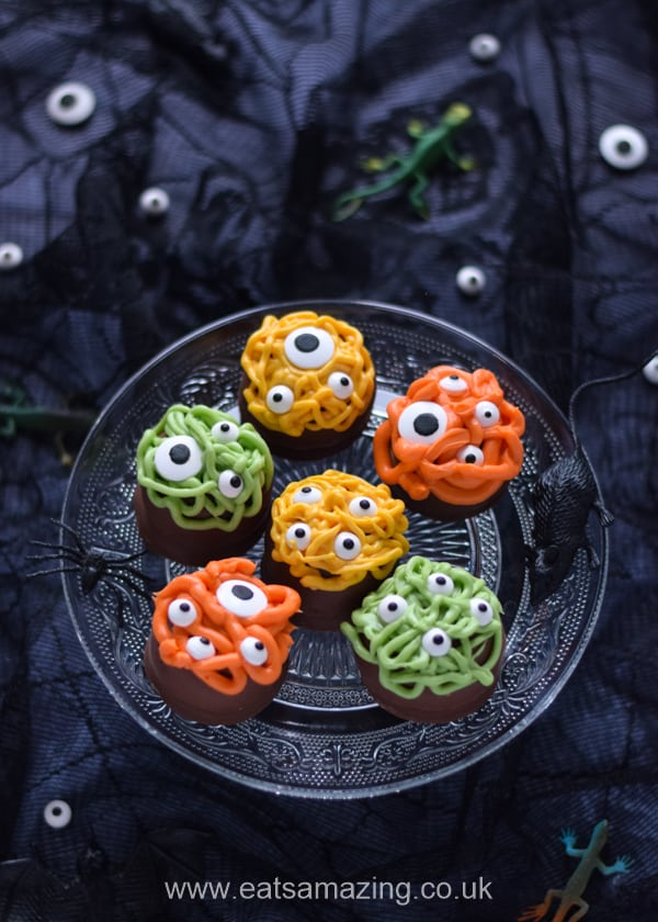 6 Halloween monster tea cakes on a glass cake stand styled for Halloween with dark backdrop